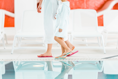 cropped view of mother and daughter in bathrobes walking near swimming pool