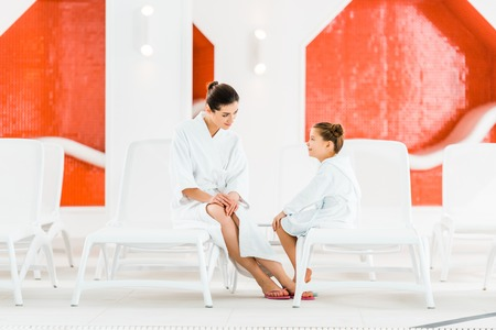 happy mother looking at daughter in bathrobe while sitting on deck chair