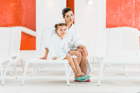 happy mother sitting with daughter on deck chairs and smiling while looking at camera