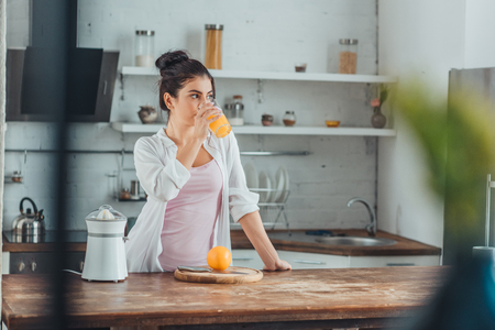 young woman drinking orange juice in kitchen during morning time at home Stockfoto