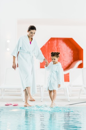 cute kid standing with mother near swimming pool and touching water with legs