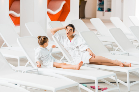 attractive mother talking with daughter in bathrobe lying on deck chair