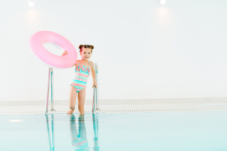 adorable kid standing in swimwear with inflatable ring and holding handrail in swimming pool