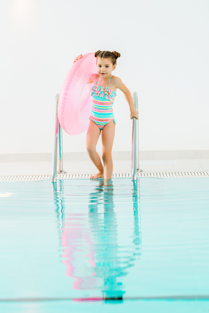 adorable kid with inflatable ring holding handrail in swimming pool Imagens