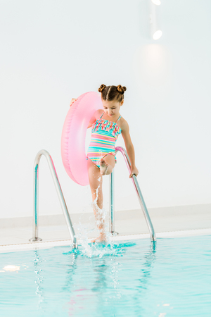 cute kid in swimwear holding handrail and playing with water in swimming pool