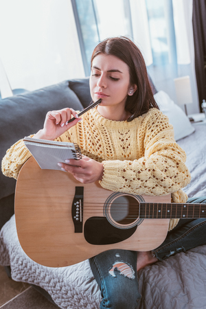thoughtful girl sitting with acoustic guitar and textbook on bed at home