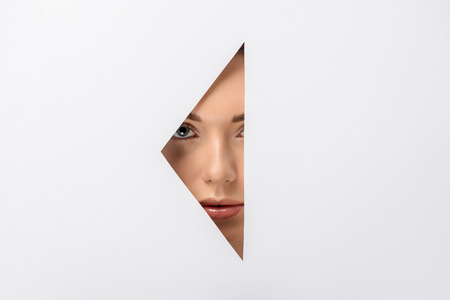 beautiful young woman looking at camera through hole on white