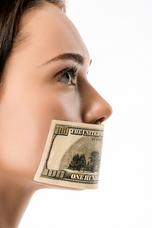 close-up view of woman with dollar banknote on mouth looking away isolated on white Archivio Fotografico - 118212024