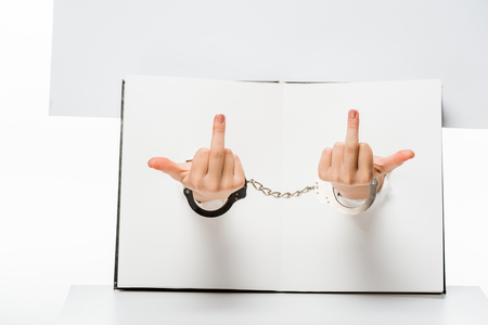 cropped shot of female hand in handcuffs showing middle fingers through holes on white