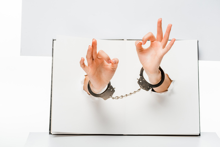 partial view of female hands in handcuffs showing ok sign through holes on white