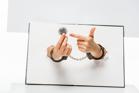 partial view of female hands in handcuffs holding bitcoin through holes on white
