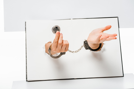 partial view of woman in handcuffs holding bitcoin through holes on white Stock Photo
