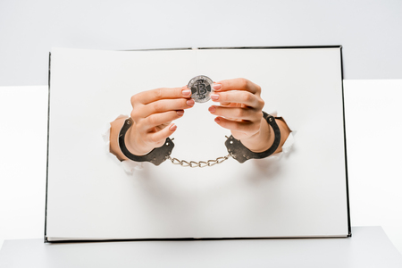 cropped shot of woman in handcuffs holding bitcoin through holes on white Stock Photo - 118485934