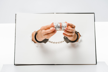 cropped shot of woman in handcuffs holding dollar banknotes through holes on white Stock Photo