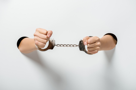 cropped image of girl in handcuffs holding hands through holes on white Stock Photo - 118487057