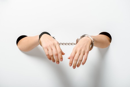cropped image of woman in handcuffs holding hands through holes on white Stock Photo - 118487058