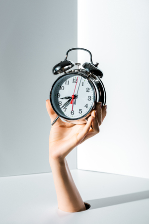 cropped image of woman holding retro styled alarm clock in hand through hole on white
