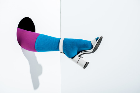 cropped image of girl showing leg in trendy violet tights, blue sock and white high heel in hole on white