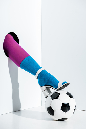 cropped image of girl putting leg in stylish violet tights, blue sock and white high heel on football ball through hole on white