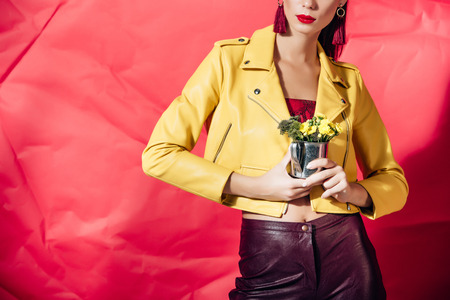 cropped view of woman in yellow leather jacket posing with flowers on red background Stock Photo
