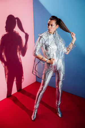 stylish girl posing in metallic bodysuit and trendy raincoat for fashion shoot on pink and blue background
