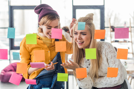 beautiful casual businesswomen laughing near colorful sticky notes on glass window in office