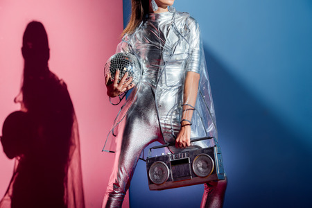 cropped view of fashionable woman in silver bodysuit and raincoat posing with boombox and disco ball on pink and blue background Stockfoto