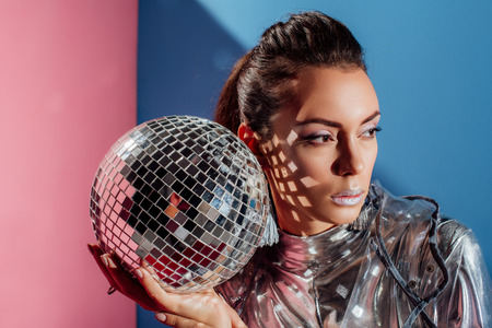 beautiful stylish young woman posing with silver disco ball on pink and blue background Banco de Imagens