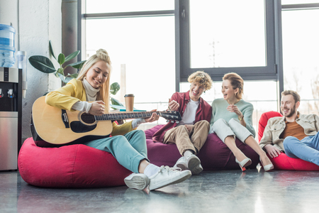 happy group of friends sitting on bean bag chairs and playing guitar