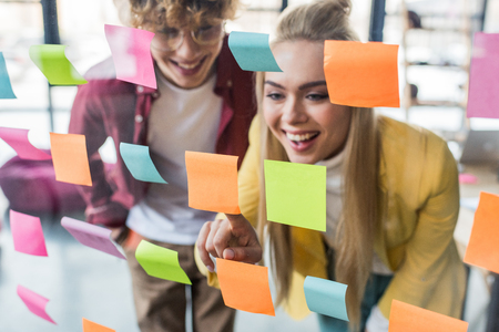 happy casual businessman and businesswoman putting colorful sticky notes on glass window in office