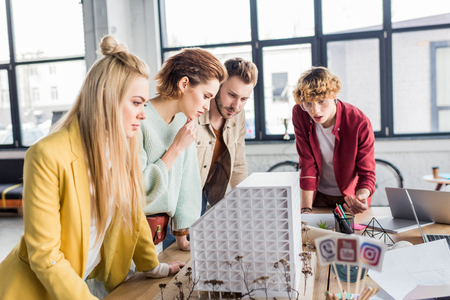 concentrated group of female and male architects working together on house model in loft office