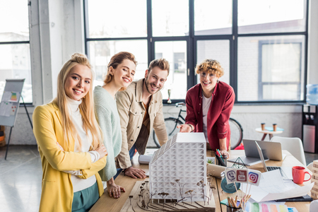 smiling group of female and male architects working together on house model in loft office Stock Photo