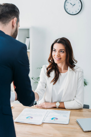 selective focus of beautiful advisor shaking hands with investor at workplace