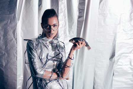 attractive young model in silver bodysuit and raincoat holding fish on metallic background Фото со стока