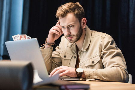 handsome casual businessman sitting at table and using laptop in office