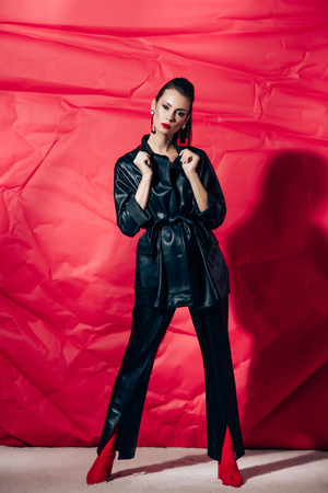 attractive fashionable young woman posing in black leather suit on red background