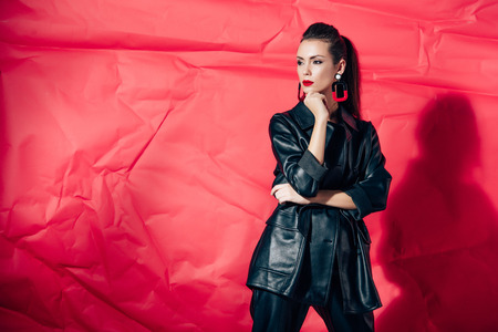 fashionable young woman posing in black leather suit on red background
