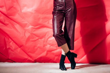 low section view of model posing in burgundy leather pants on red background