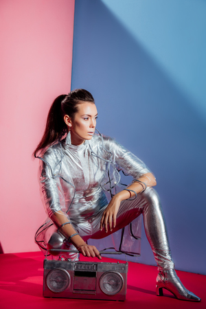 fashionable young woman in silver bodysuit and raincoat posing with boombox on pink and blue background Banco de Imagens