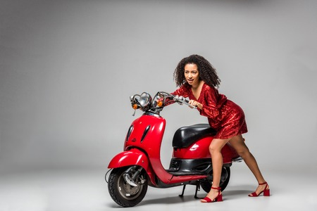 beautiful african american girl in red dress posing with motor scooter on grey background