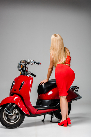 back view of girl in red dress posing with motor scooter on grey background Stok Fotoğraf