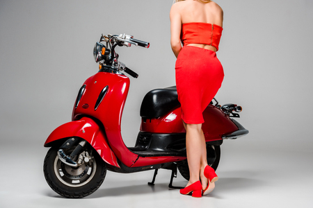 cropped view of girl in red dress posing with motor scooter on grey background