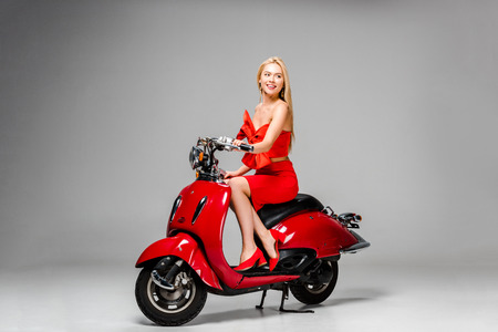 beautiful smiling girl in red dress posing while sitting on motor scooter on grey background