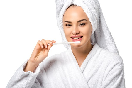 beautiful girl in bathrobe holding toothbrush, smiling and looking at camera isolated on white