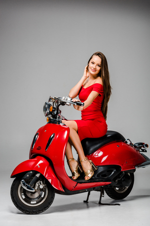 attractive smiling girl in red dress sitting on motor scooter and looking at camera on grey background