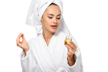 attractive girl in bathrobe looking at opened bottle of oil isolated on white