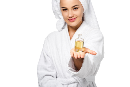 attractive girl in bathrobe showing bottle of oil and looking at camera isolated on white