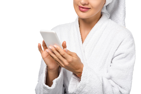 attractive girl in bathrobe using smartphone isolated on white
