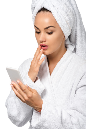 surprised girl in bathrobe looking at smartphone screen isolated on white Stock Photo