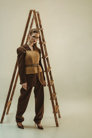 attractive woman in vintage style posing near wooden ladder on beige